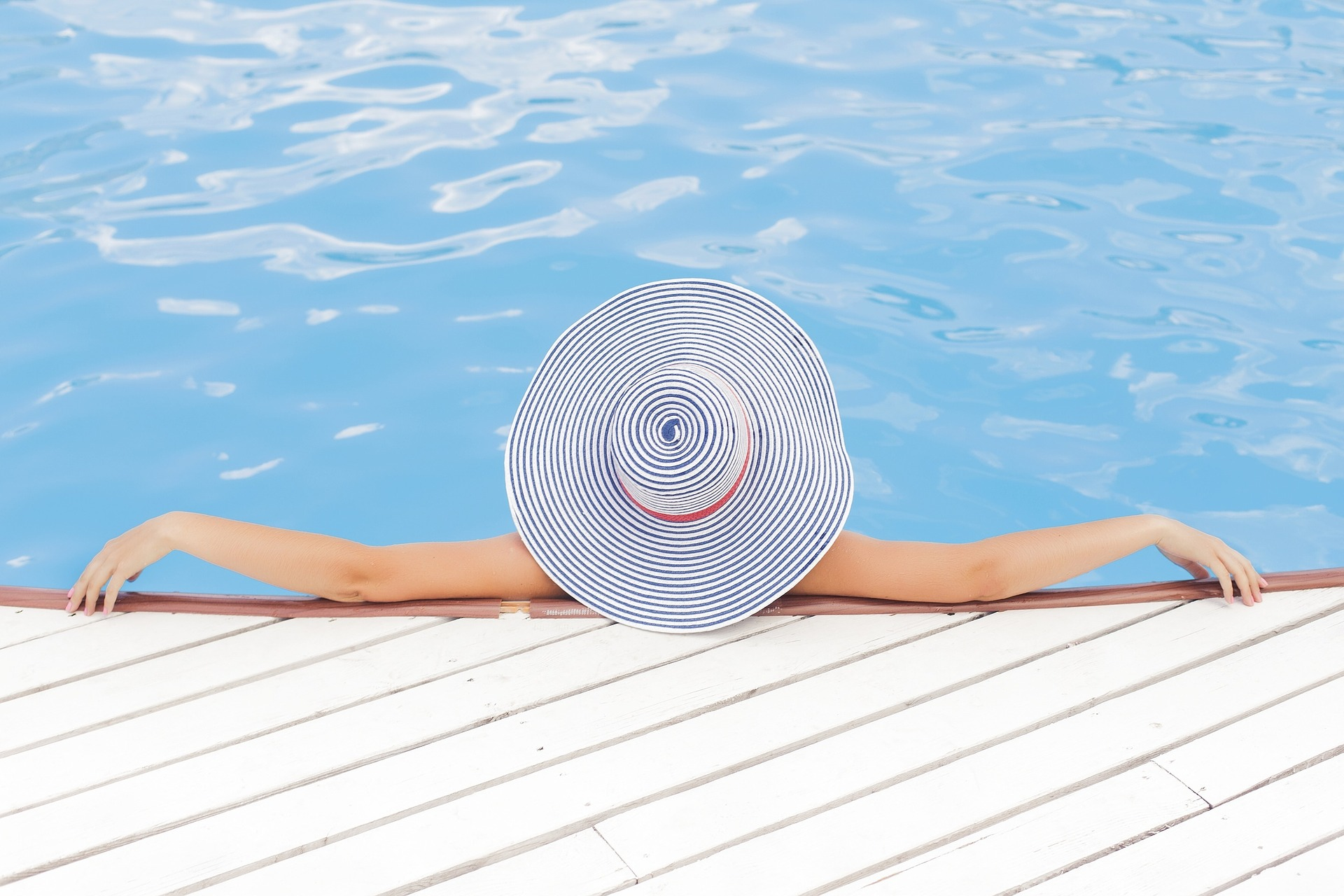 woman lounging in a pool with a sun hat