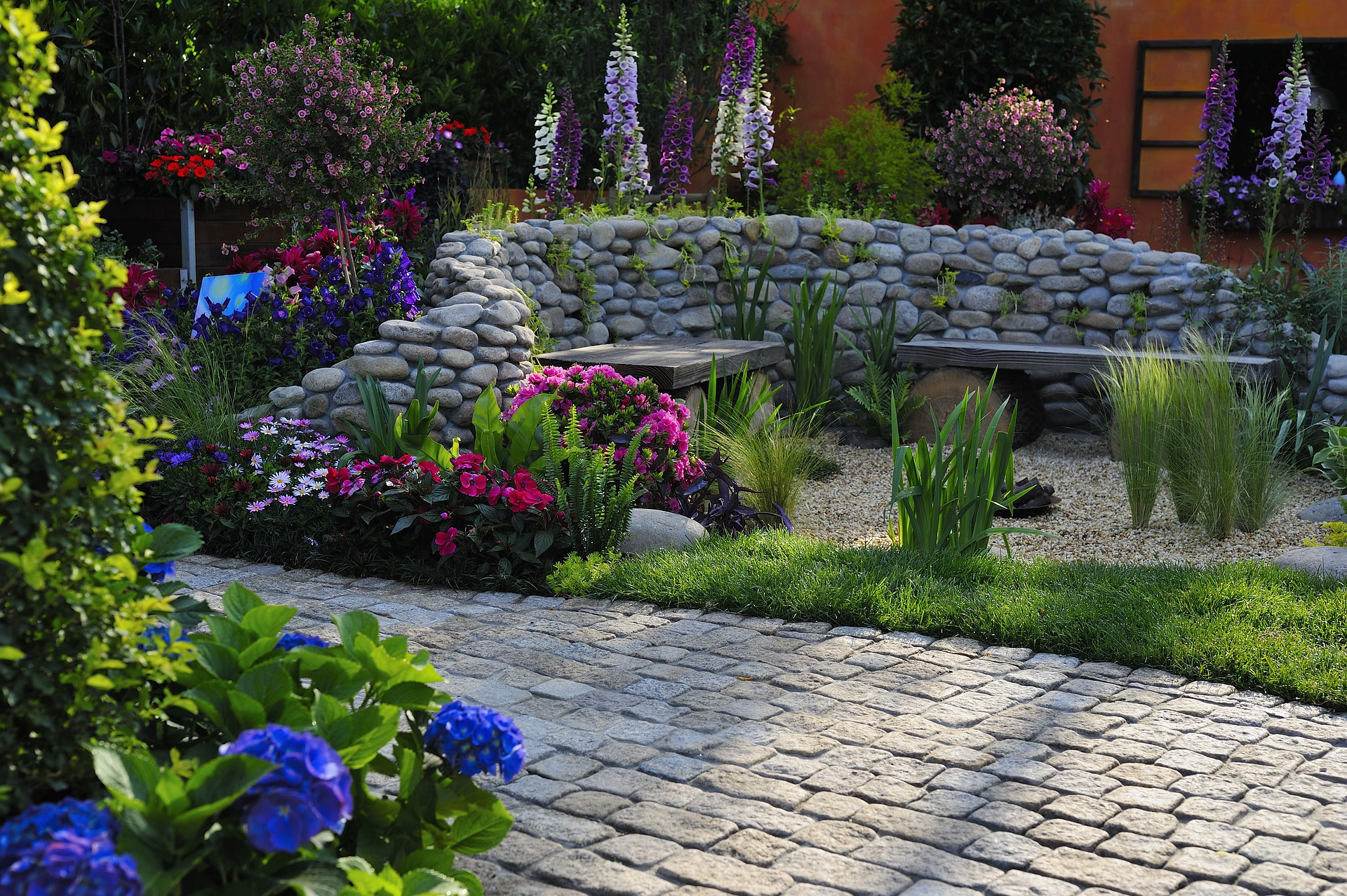 green garden with blue and purple flowers and stone pathway