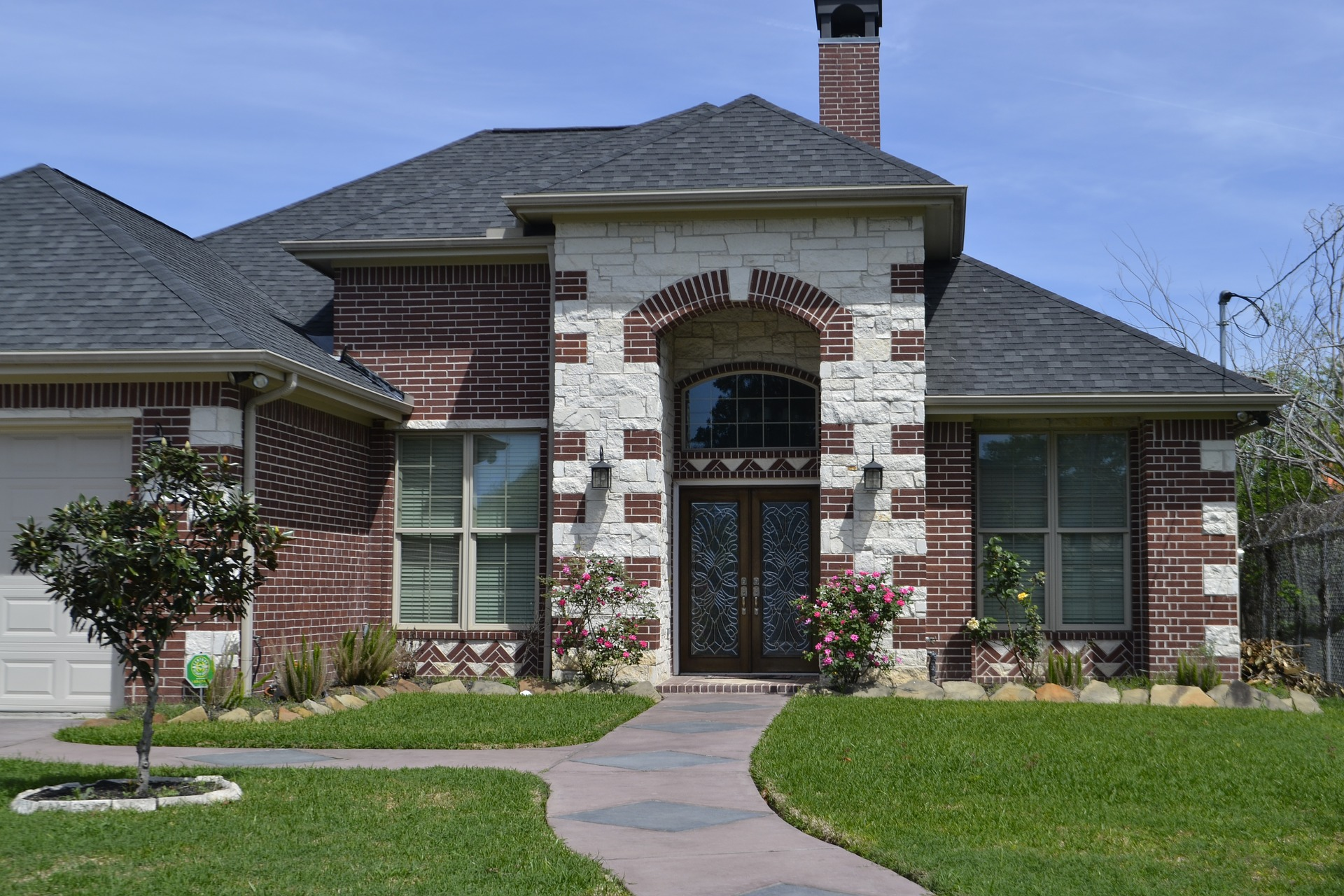 front entrance to a large brick home, beautifully manicured front lawn and landscape design