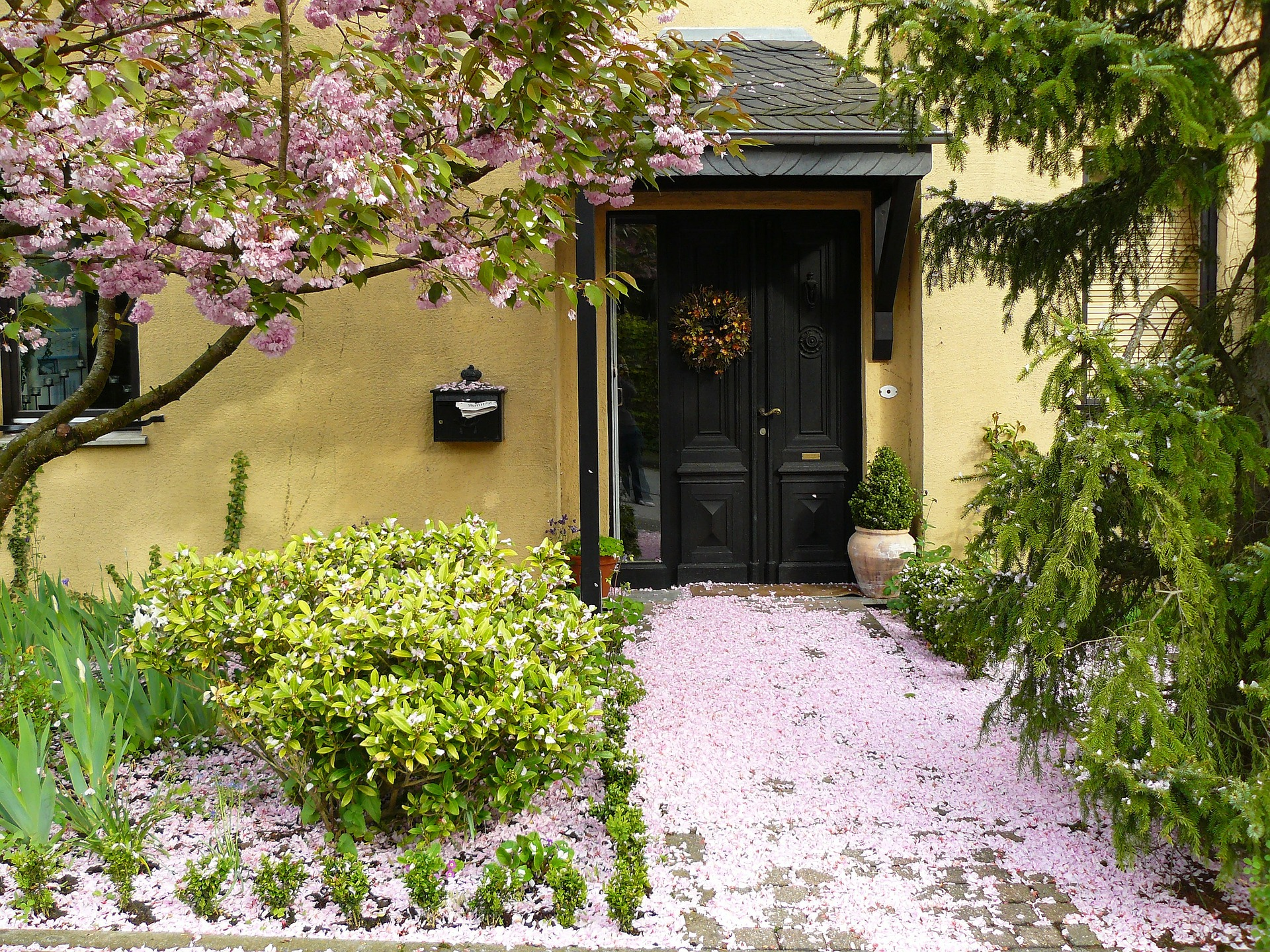 entrance to home with black door, trimmed trees, flowers and bushes